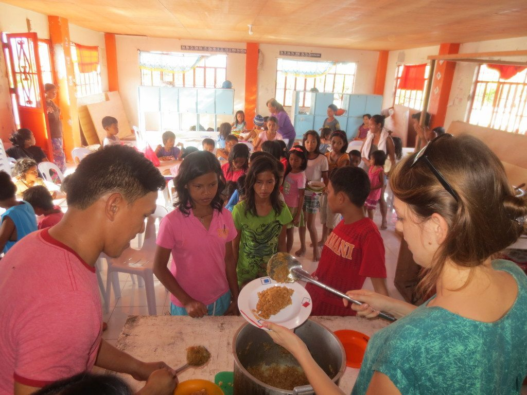 Elsa and her boyfriend serving food at her community center in the philippines