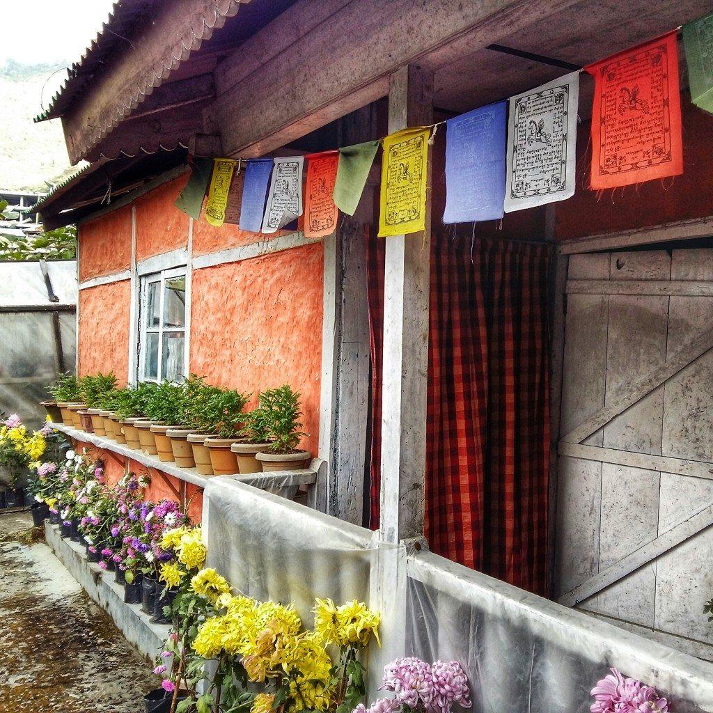 tradtional monpa house with tibetan prayer flags in Bombila, Arunachal Pradesh