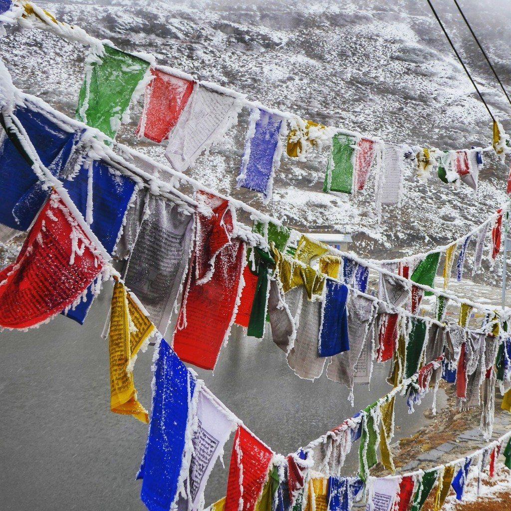 frozen colourful tibetan prayer flags in tawang