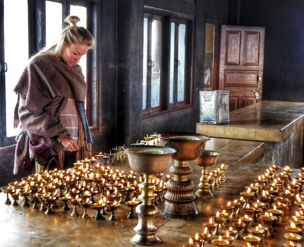 lighting a yak butter lamp in a Tibetan Buddhist monastery in Tawang
