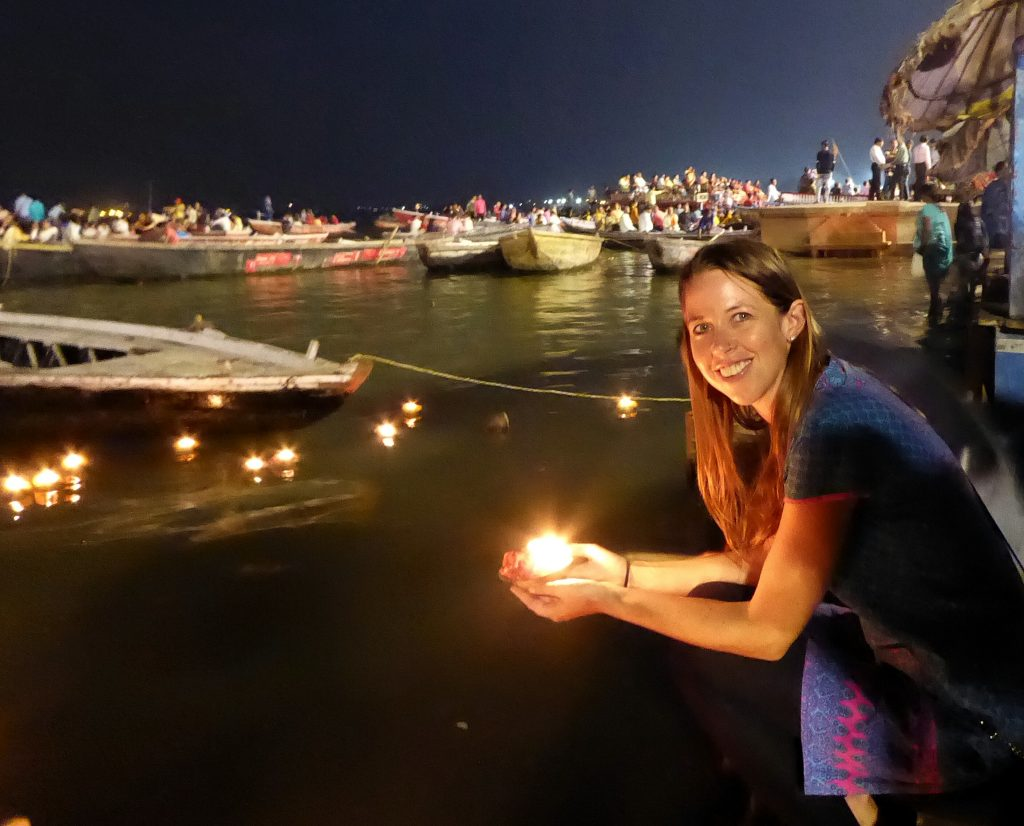 Lighting a diya (candle) on the ghats of the River Ganges in Varanasi
